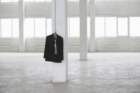 hangs: Suit jacket hangs on pillar in empty warehouse