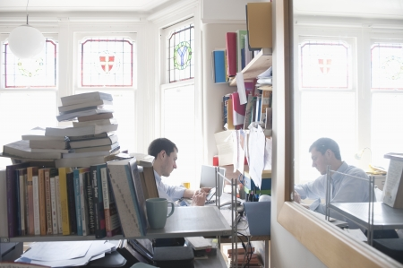 untidy: mid adult man working in cluttered study