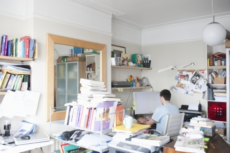 untidy: Creative professional sits at computer in corner of office