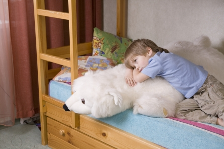 5 year old: 5 year old boy lies on bunk bed with polar bear soft toy