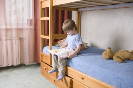 bunkbed: 5 year old boy sits on bunk  bed reading a book