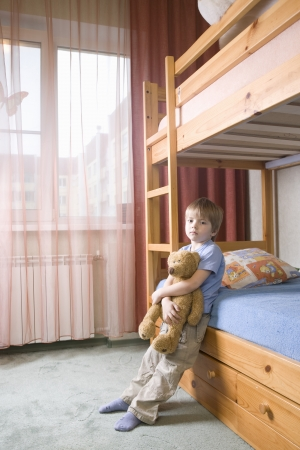 bunkbed: 5 year old boy leans on bunk bed holding teddybear