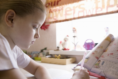 niños estudiando: Niña de 10 años se sienta en la mesa de la ventana haciendo su tarea LANG_EVOIMAGES