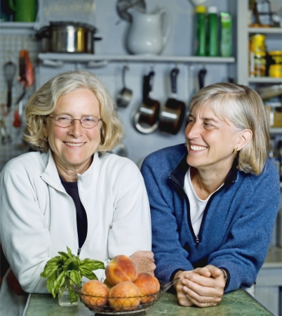 homeware: Two mature women lean on kitchen counter smiling