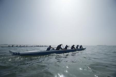 水の上のアウトリガー カヌー チーム