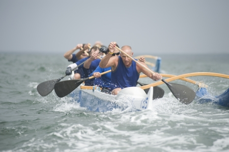 Outrigger canoeing team on water Stock Photo