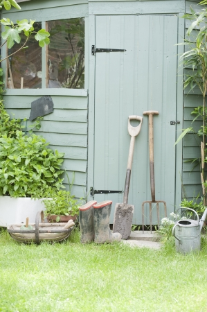 Gardening tools lean against door of potting shed Stock Photo