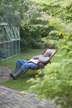 Gardener dorme sulla sdraio nel giardino sul retro