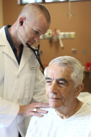 geriatrician: Young doctor listens to young elderly mans breathing