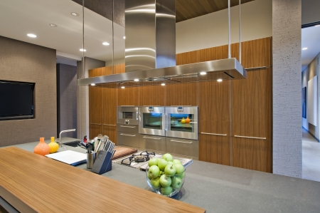 integral oven: Wood panelled spotlit kitchen in California home