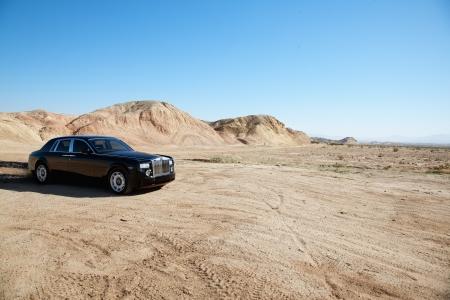 unpaved road: Rolls Royce car leaving trail of black oil behind on unpaved road