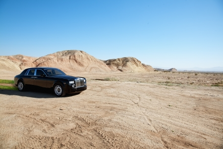 unpaved road: Black eco-friendly Rolls Royce car running off-road on unpaved road