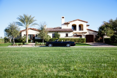 Luxurious car parked outside house in front yard Stock Photo