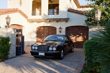 Luxurious car parked in entrance gate of house
