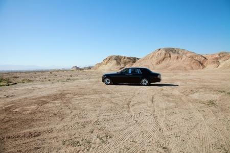unpaved road: Rolls Royce car parked on unpaved road with tire tracks