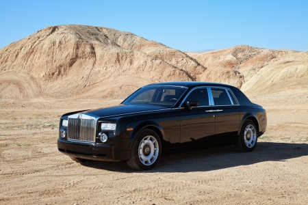 Rolls Royce car parked on unpaved road in front of mountains Stock Photo