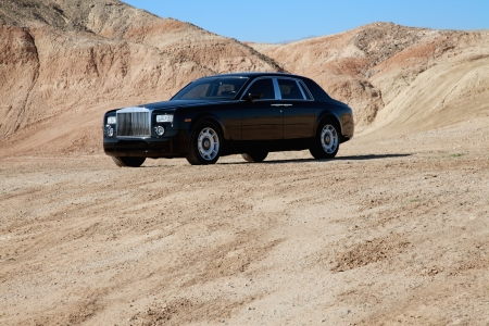 unpaved road: Rolls Royce car parked on unpaved road with mountains in background