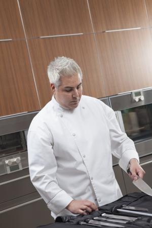 wood panelled: Mid- adult chef chooses knife
