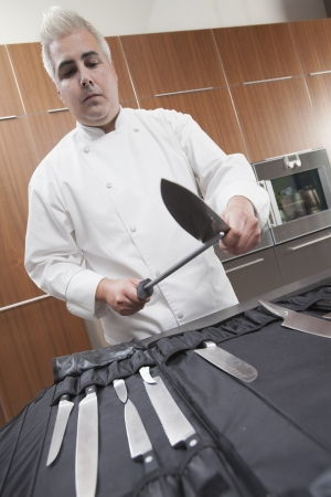 wood panelled: Mid- adult chef sharpens knife