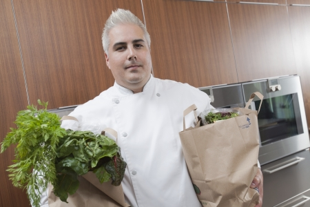 wood panelled: Mid- adult chef with two bags of fresh groceries LANG_EVOIMAGES