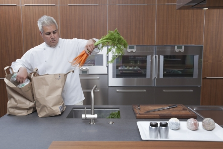 wood panelled: Mid- adult chef lifting carrots into sink LANG_EVOIMAGES