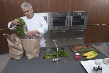 wood panelled: Mid- adult chef unpacking groceries