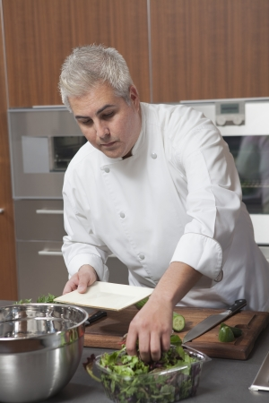wood panelled: Mid- adult chef prepares salad