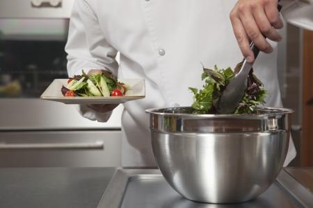 side plate: Mid- adult chef lifts leaf vegetables onto side plate LANG_EVOIMAGES
