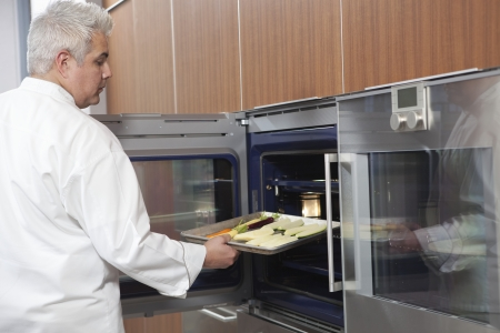 Mid- adult chef places baking tray in oven Stock Photo - 20741388