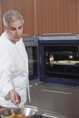 wood panelled: Mid- adult chef checks pan on hob