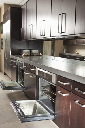 wood panelled: Dark wood kitchen with open oven doors