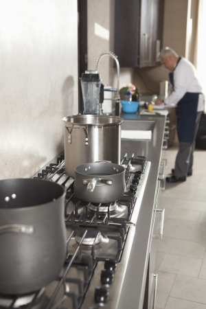 Chef works in kitchen with saucepans on hob Stock Photo - 20741438