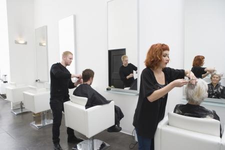 unisex: Estilistas cortan el pelo de los clientes en el sal�n unisex