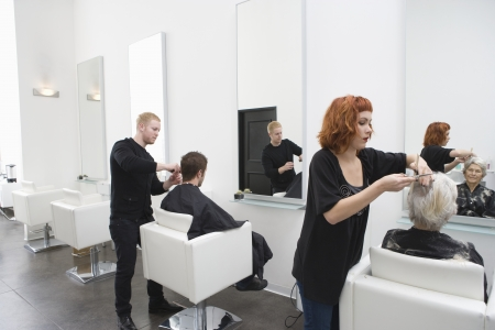 cutting hair: Stylists cut clients hair in unisex salon