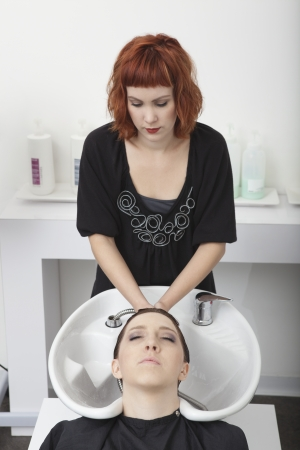 shampooing: Hairdresser shampooing female client in salon basin
