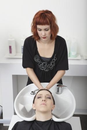 riverside county: Hairdresser shampooing female client in salon basin