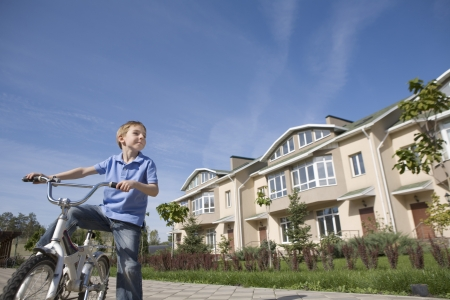 neighbours: Boy stands with bicycle in new housing development LANG_EVOIMAGES