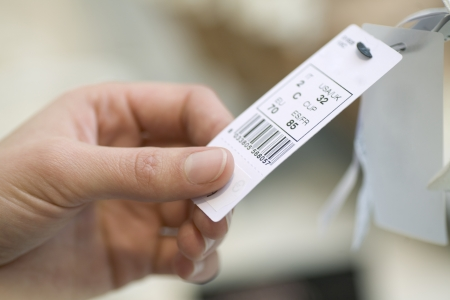 Close up of ladies hand holding a clothes tag