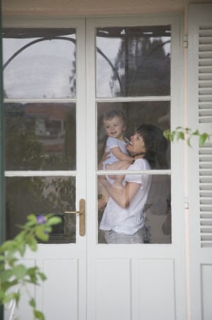 view through door: Mother and toddler standing inside a door with glass windows