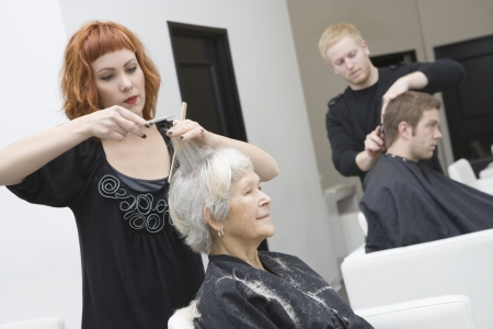 cutting hair: Stylist cuts elderly womans hair