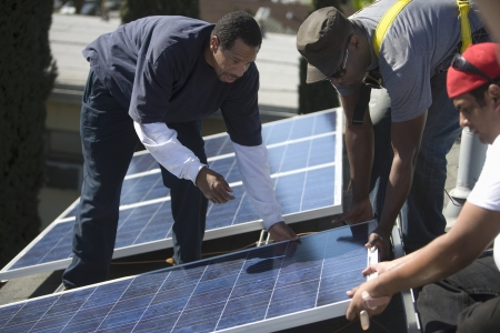 A group of men lifting a large solar panel