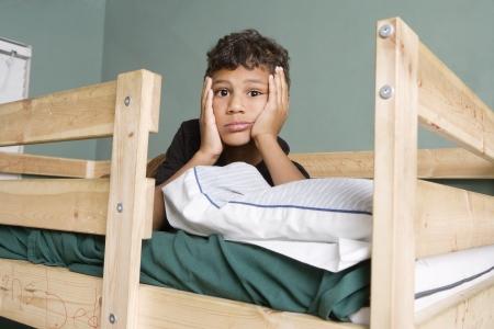 bunkbed: Tired multi ethnic boy lying on bed