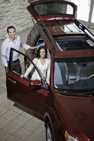 show room: Happy couple in luxury car show room LANG_EVOIMAGES