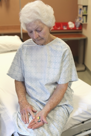 three person: An old lady in a hospital gown  sitting on a bed  looking down at several pills in her hand