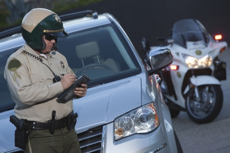 traffic ticket: Patrol officer stands witing ticket