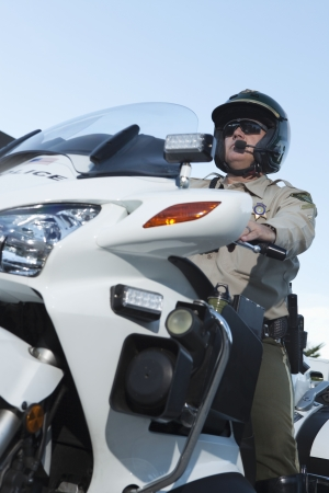 a white police motorcycle: Patrol officer sits on motorcycle