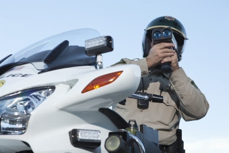 motorcycle officer: Patrol officer sits on motorcycle looking through pseedometer