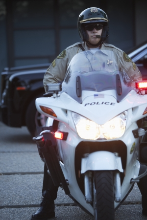 motorcycle officer: Patrol officer sits on motorcycle with hazrd lights lit LANG_EVOIMAGES