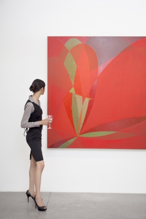 art gallery: Full length of a woman looking at painting in art gallery