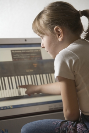 Child leans keywboard on computer with touch screen technology Stock Photo - 20741803